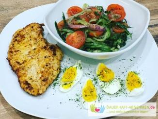 Gurkensalat mit Tomaten und roten Zwiebelringen und Hühnchenfilet