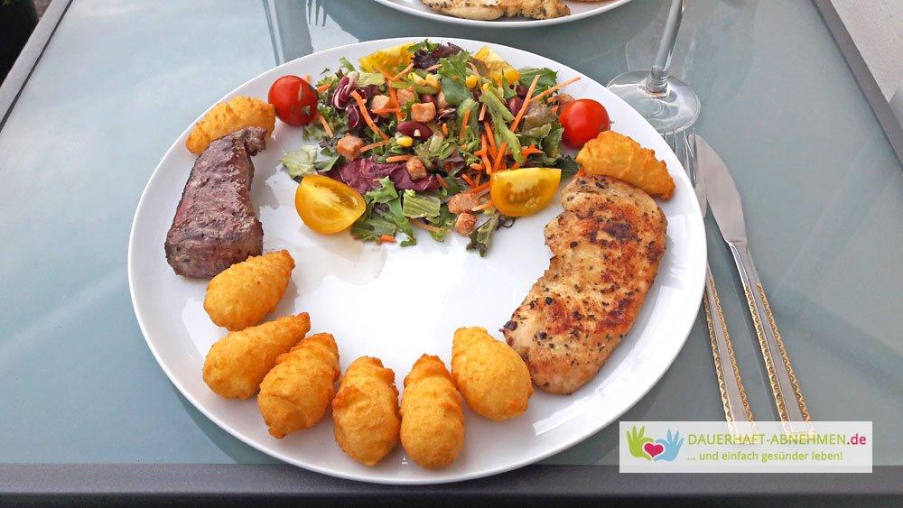 Fleisch mit Salat und Kroketten