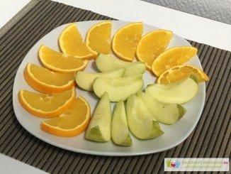 Obstteller mit Orange und Apfel