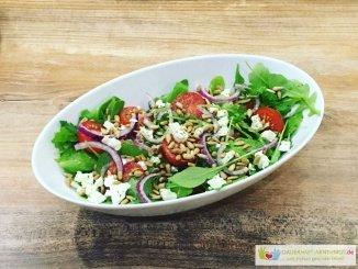 Salat aus Rucola, Zwiebel, Fetakäse und Tomaten